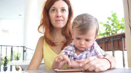 travessura : a little boy with mom uses the Internet on Smartphone Vídeos