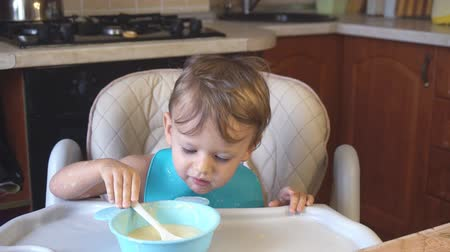 aveia : little boy eats porridge for breakfast