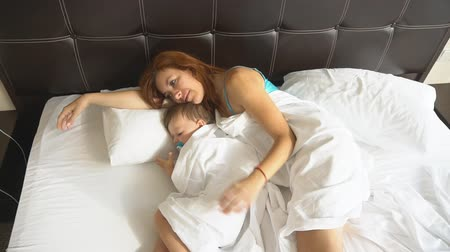 yatak kıyafeti : mom and son sleep in the morning in bed at Stok Video