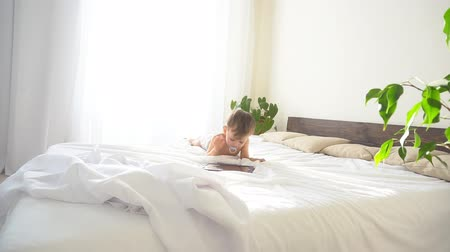 oneperson : little son lies on the bed in the bedroom and looks at Internet Tablet