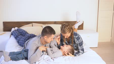 yatak kıyafeti : mom dad and son in the morning lying on the bed at home