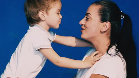 žolík : mother and son play laugh and kiss on a blue background
