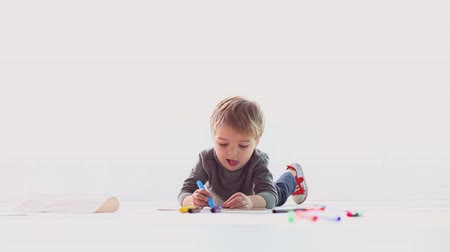small pen : little boy draws colored pencils on paper