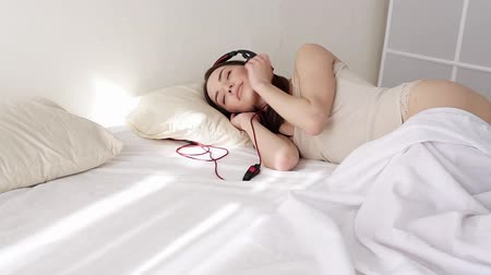 izlenim : woman in lingerie lying in the bedroom listening to music from big headphone