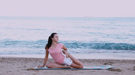 energy balance : the girl is engaged in gymnastics, yoga on the beach of the sea coast Stock Footage