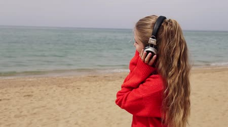 latinamerican : girl listens to music in large headphones on the beach by the sea