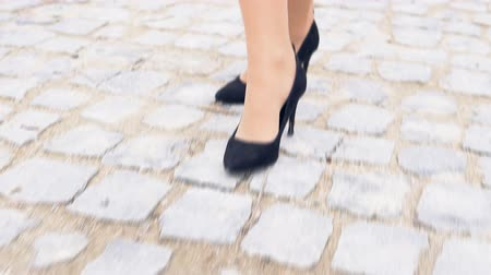 прижиматься : womens legs in black shoes on a stone road Стоковые видеозаписи