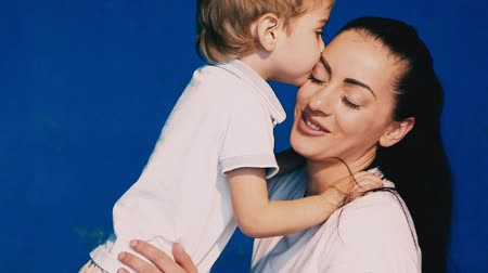 blueeyes : mother and son play laugh and kiss on a blue background