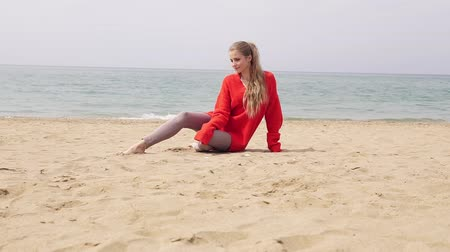 fulllength : blonde girl is sitting on the sand by the sea and posing for a photo shoot