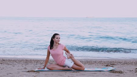 гимнастика : the girl is engaged in gymnastics, yoga on the beach of the sea coast Стоковые видеозаписи