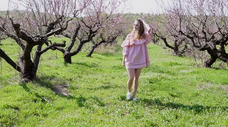 garden route : in the garden of flowering trees goes blonde girl in pink dress