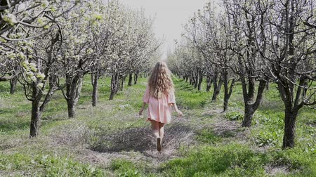 longhair : blonde girl walking on a blooming garden and resting