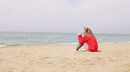 longhair : one girl sits on a sandy beach and looking at the sea