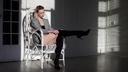 hardal : fashionable woman in the jacket sits in a white armchair in room Stok Video