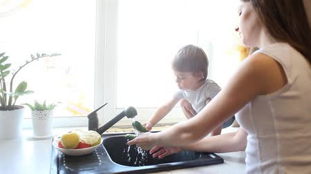 fele olyan hosszú : mother and son wash vegetables in the kitchen Stock mozgókép