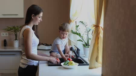 фрукты : boy and mom washed vegetables in the kitchen