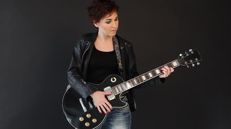fekete fehér : female musician playing the guitar in a black room