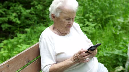 foster : old granny looks at Internet smartphone Stock Footage