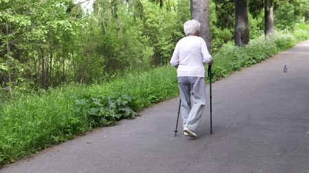 walkers : grandmother walks with Nordic walking sticks Stock Footage