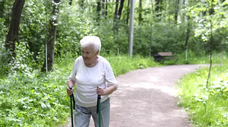 common : old granny goes with sticks for walking on the road