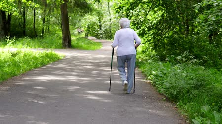 jardim : Grandma walks in the park with sticks for Nordic walking