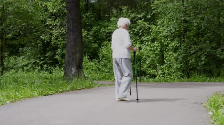 引退する : Grandma walks in the park with sticks for Nordic walking in retirement