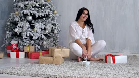 narożnik : pregnant mom at Christmas tree looking Christmas gifts