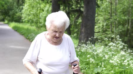 bengala : grandmother walks with Nordic walking sticks old grey