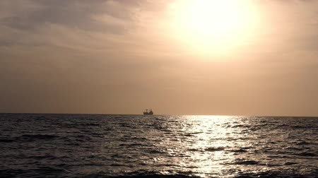 industrial fishing : Golden sunset with silhouettes of sea going vessels, tankers Stock Footage