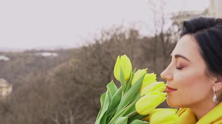 Cheerful brunette woman enjoying smell of yellow tulips given by beloved man Vidéos Libres De Droits