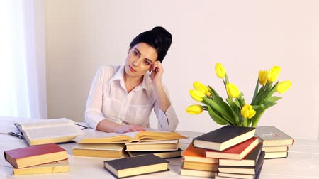 Too much work tired sleepy young woman sitting at her desk with books