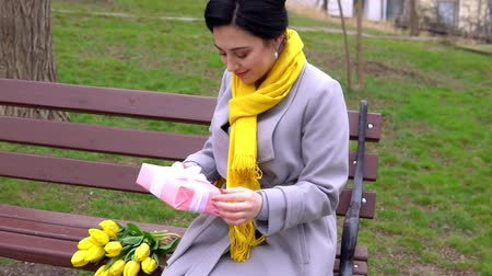 Cheerful brunette woman enjoying smell of yellow tulips given by beloved man Stok Video