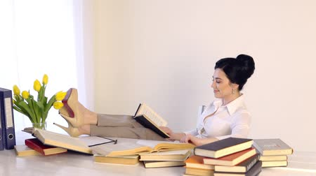 female sitting at her workplace and laughing while reading holding book Filmati Stock