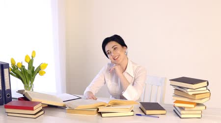 female sitting at her workplace and laughing while reading holding book Stok Video