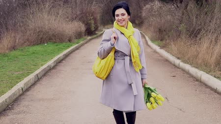 brunette woman in coats with yellow tulips