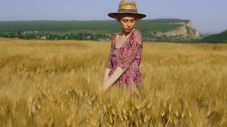 fashionable woman farmer in field of wheat harvesting rye