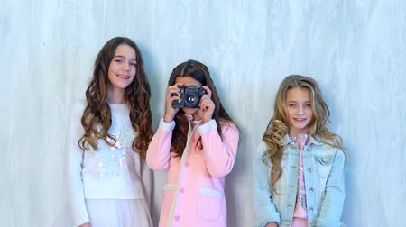 three schoolgirl girls take pictures