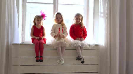 колготки : three little girls sitting on a white window Стоковые видеозаписи