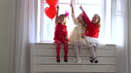 three little girls sitting on a white window Stok Video