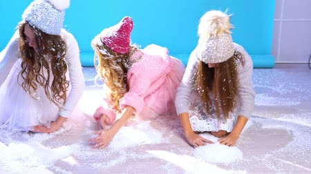three beautiful girls in a hat play in the snow Stok Video