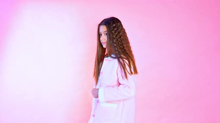 Beautiful fashionable girl poses on a pink background