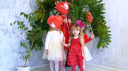 Kids friends with red balloons on holiday