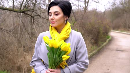gyengéd : Cheerful brunette woman enjoying smell of yellow tulips given by beloved man Stock mozgókép