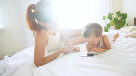 an : Mom and son watching smartphone in bedroom Stok Video