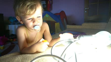 fortress : Little boy plays with light garlandgarlands Stock Footage