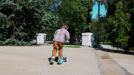školák : Child rides a scooter in a park. Carefree childhood