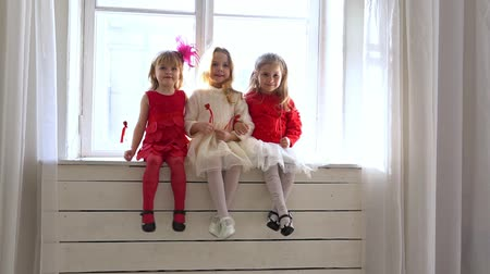 rajstopy : three little girls sitting on a white window Wideo