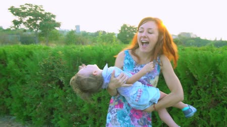louvor : Mom circles little son in her arms at sunset