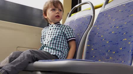 inside bus : Little boy rides on public transport Stock Footage