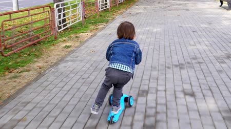 terlik : Child rides a scooter in a park. Carefree childhood